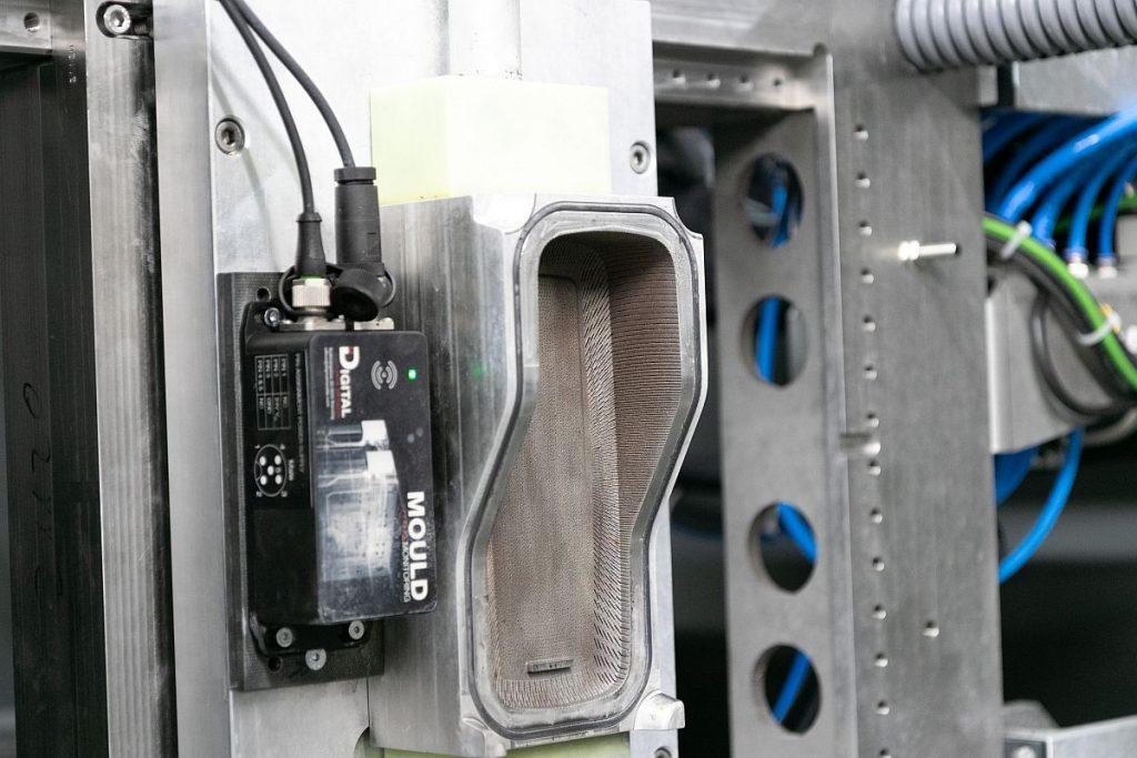 Blick in die Maschine: Das 3D-gedruckte Schäumwerkzeug ist zudem mit der Mould-Monitoring-Box von Digital Moulds ausgerüstet. - Bild: Hofmann Werkzeugbau