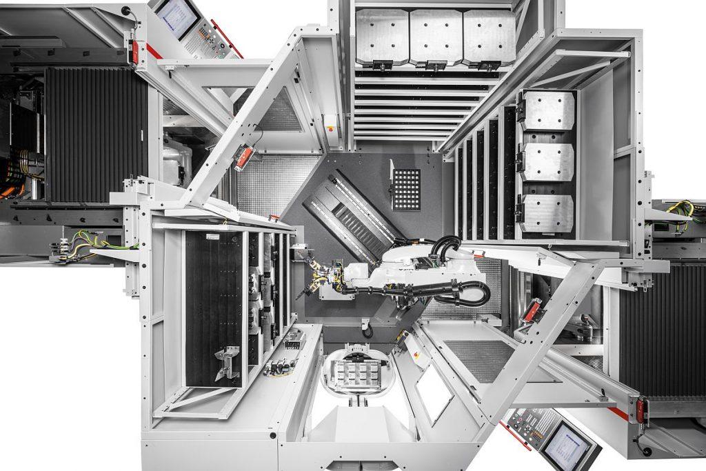 Das Robotersystem RS 1 von oben: Hier versorgt es  zwei Hermle Bearbeitungszentren C 22 U links und rechts – bis zu drei Speichermodule sorgen für eine lange autonome Laufzeit. Sie nehmen unter anderem Paletten, Universalmatrizen und Greifer auf. - Bild: Hermle