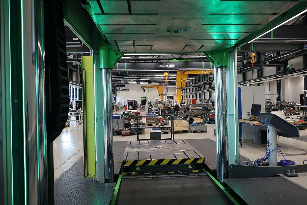 Mit unübersehbaren Lichtsignalen an den Säulen – hier grün – zeigt die Tuschierpresse ihren Zustand an. Alles ist auf Sicherheit, Effizienz und Qualität getrimmt. Blick durch die Presse in die neue Montagehalle bei Hofmann. - Bild: Pergler Media